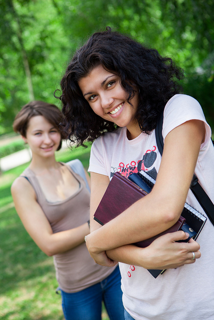 Two girls with school textbooks. Image courtesy of CollegeDegrees360 on Flickr.