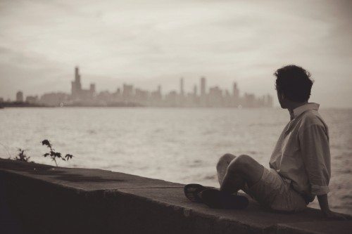 A man looking out onto a river in front of a city.