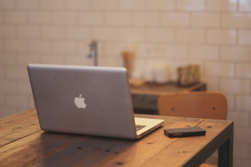 Laptop and phone on a wooden desk.